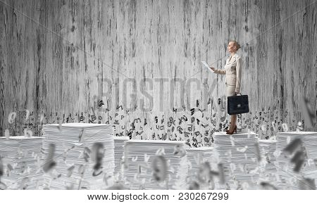 Confident Business Woman In Suit Standing Among Flying Letters With Grey Wall On Background. Mixed M