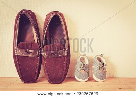Father And Baby Shoe  On Wooden Table