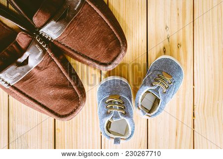 Father And Baby Shoe  On Wooden Background
