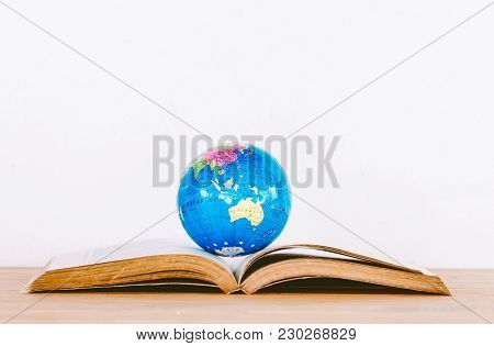 Global Ball On Book On Wooden Table