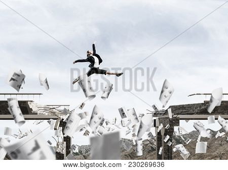 Business Woman Jumping Over Gap In Bridge Among Flying Papers As Symbol Of Overcoming Challenges. Sk