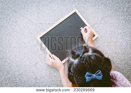 Little Girl Writing Something On A Blackboard