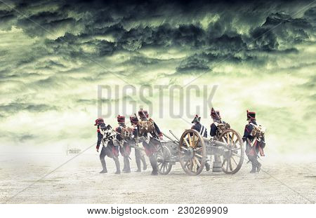 Napoleonic Soldiers Marching And Pulling A Cannon In Plain Land. Countryside With Stormy Clouds. Sol