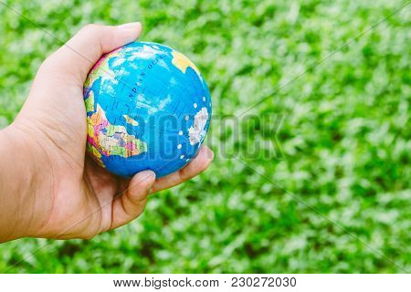 Hand Holding Model Of The Globe On Green Background