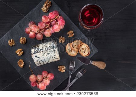 An Overhead Photo Of A Piece Of Blue Cheese With Vibrant Grapes, Slices Of Bread, Nuts, And A Glass
