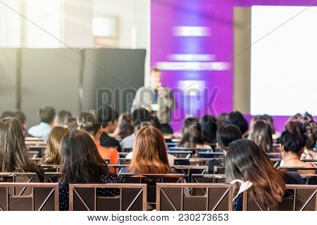 Rear View Of Audience In The Conference Hall Or Seminar Meeting Which Have Speaker In Front Of The R
