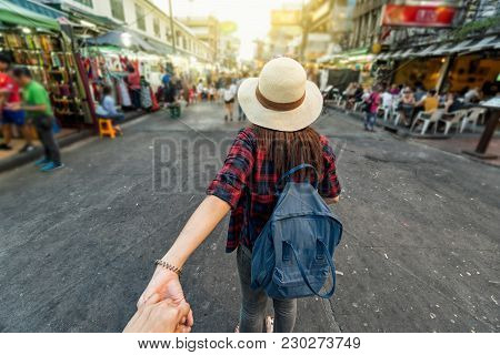 Back Side Of Young Asian Traveling Women Leading By Holding Her Boyfriend Hand In Khaosan Road Walki