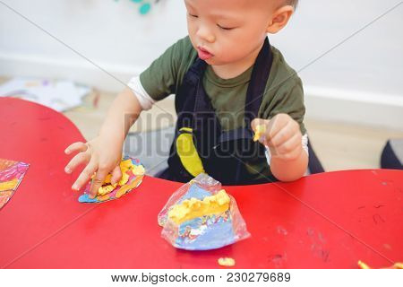 Cute Asian 18 Months Old Toddler Boy Child Playing Modeling Clay / Play Dought At Play School, Creat