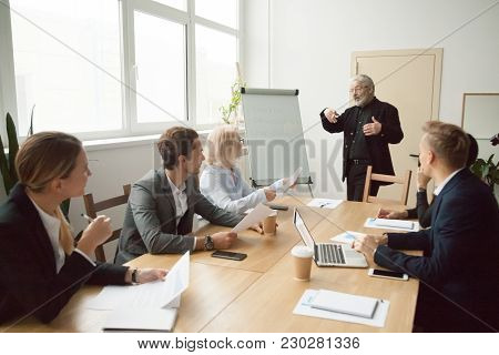Experienced Business Coach Giving Presentation To Executive Managers Team Explaining Strategy With F