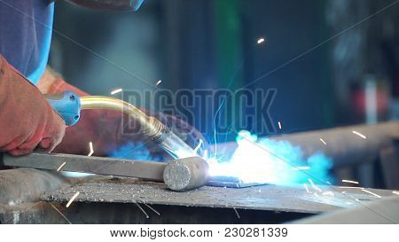 Worker With Protective Mask Welding Metal. A Man Welds A Metal With A Welding Machine. Welder Is Wor
