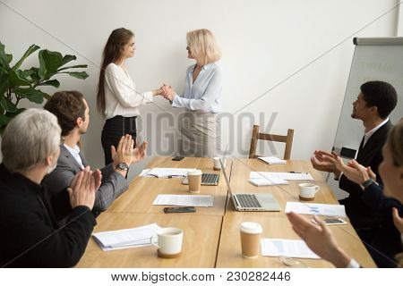 Senior Businesswoman Boss Promoting Female Employee Thanking For Good Work Holding Hands As Trust An