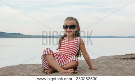 One Beautiful Teenage Girl With Brown Hair Outside On A Beautiful Summer Day. The Child Is Sitting O