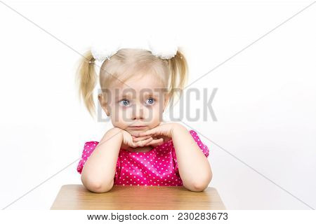 A Beautiful Young Blond Girl Leans Her Elbows On A Chair And Puts Her Head On Her Hands.