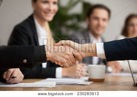 Hands Of Senior And Young Businessmen Shaking At Group Meeting, Two Partners Of Different Age Handsh