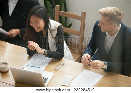 Attractive Asian Businesswoman And Caucasian Businessman Laughing Talking At Group Meeting, Multirac