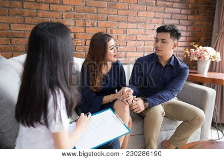 Two Asian Couple Consulting About Their Problem With Professional Doctor Or Psychologist
