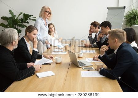 Dissatisfied Senior Woman Boss Scolding Employees For Bad Work At Diverse Group Meeting, Angry Femal