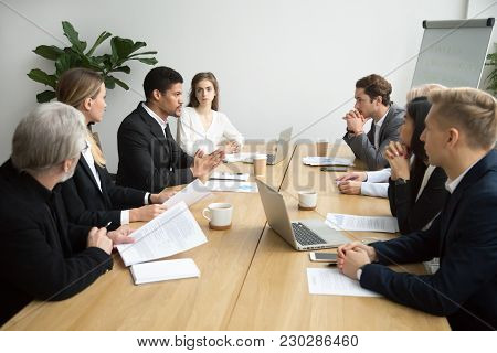 Focused Black Team Leader Talking To Colleagues At Meeting Sitting At Conference Table, Serious Afri