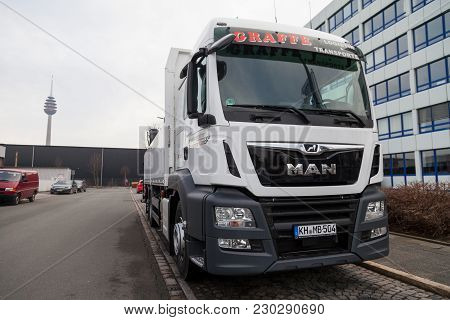 Nuernberg / Germany - March 4, 2018: Man Flatbed Truck With Crane Stands On Roadside In A Industrial