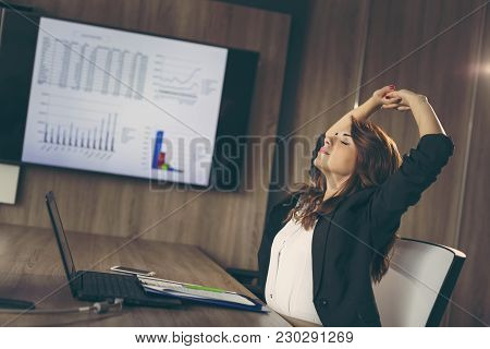 Businesswoman Working Overtime, Sitting In An Office, Stretching While Working On A Laptop Computer