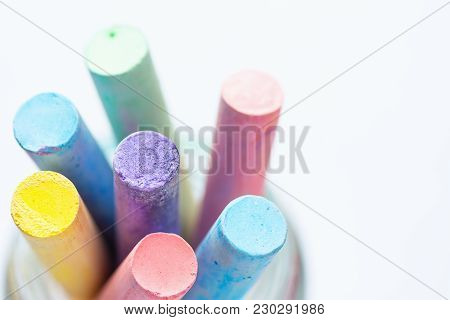 Bunch Of Multicolored Chalks Crayons In Pencil Cup. Top View White Background. Education Arts Crafts