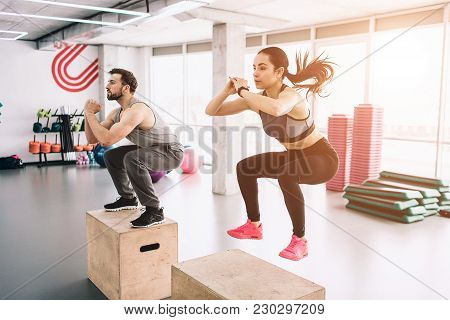 A Picture Of Slim And Well-built Young Man And Woman Doing Jumps On Platform. It Is A Hard Exercise