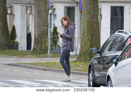 Young Woman Walks On The Crosswalk And Checks Her Smartphone For Messages And Does Not Pay Any Atten