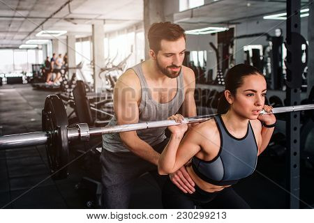 Cut View Of A Guy Helping And Supporting Her Girlfriend To Do Squats In Smith's Machine In A Right W