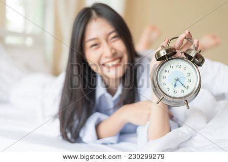 Blur Beautiful Woman Showing An Ancient Copper Alarm Clock In  Hand To Camera After Wakeup In Bed.ha
