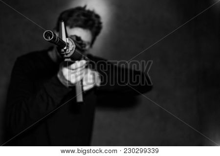 White Male Aimming An Assault Riffle To The Left Of Camera. Black And White Photo.