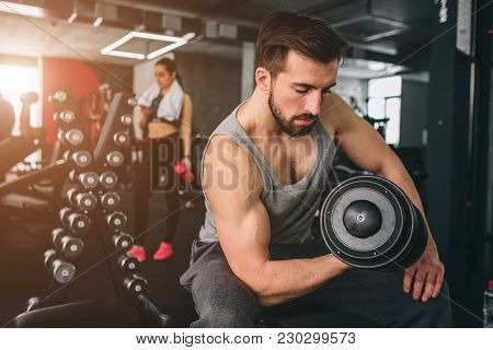 Close up of strong guy that exercising with a dumbbell on the sport bench while hir girlfriend is standing nearby, resting an looking to the phone poster