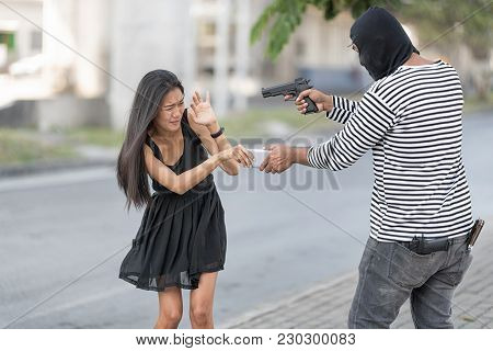 A Robber Is Rob The Mobile Phone From A Black Dress Woman By The Gun. A Woman Is So Scared.