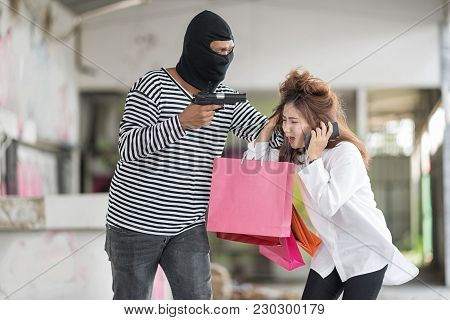 A Masked Robber Is Trying To Rob A Woman. He Is Pulling Her Hair. A Woman Is So Scared.  She Has A M