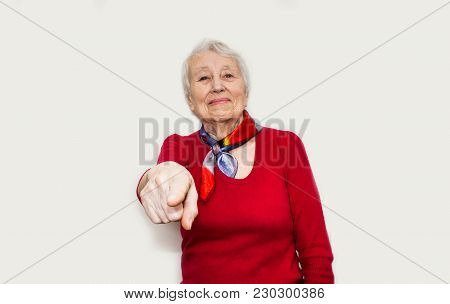 Senior Woman Pointing To Camera. Smiling Happy Senior Woman On White Studio Background. Human Emotio