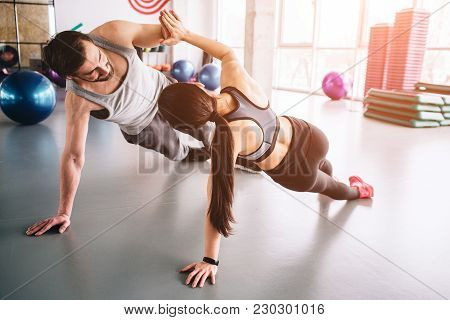 Another Picture Of Two People Standing In A Side Plank Position On One Hand And Holding Each Other W