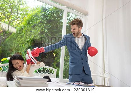 Portrait Of Aggressive Businessman In Boxing Gloves Punching His Rival Woman.