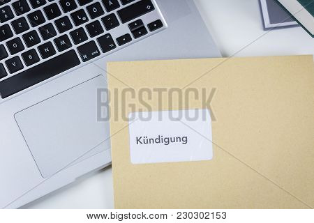 Redundancy Letter Or Dismissal In German Enclosed In A Brown Envelope Lying On Top Of An Open Laptop