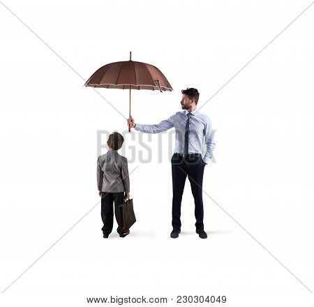 Businessman With Umbrella That Protect A Child. Concept Of Young Economy And Startup Company Protect