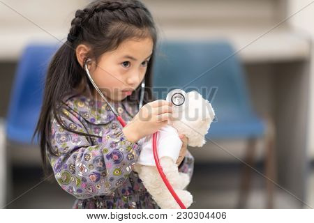 Cute Asian Girl Playing As Doctor Using Stethoscope Listening Check Heartbeat Of Teddy Bear. Educati