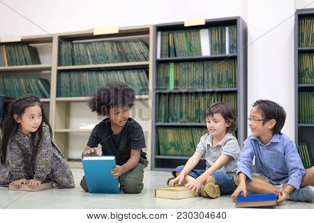 Happy Kids Reading On The Floor, Education Lifestlye In The Library. Young People Explore Lifestlye