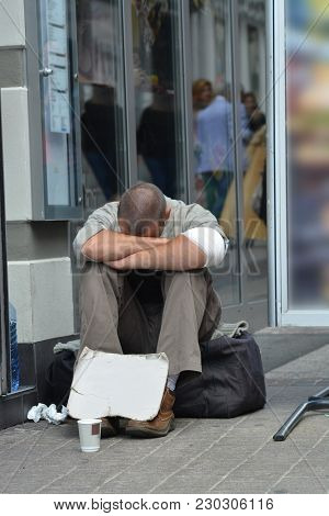 Man Sitting On The Street Asking For Money