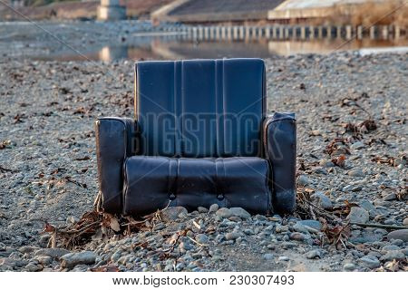 An Abandoned Living Room Chair That Was Discarded On A Rocky Sandbar In The Center Of The Sagami Riv