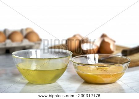 Two Bowls With An Egg Yolks And Whites On The Table With Broken Eggshells On The Background Isolated
