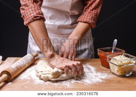 Woman Presses And Kneads The Dough. A Woman Is Kneading Pizza Dough On A Table.