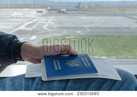 Man's Hand Is Holding Ukrainian Foreign Passport With Tickets To Airplane In Background Parked Plane