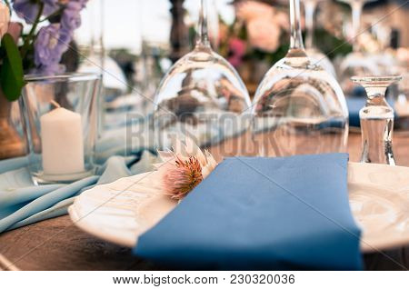 Romantic Wedding Or Another Catered Event Table Setting, Flowers, White Plates, Blue Napkin, Easter