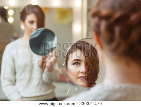 Portrait Of A Beautiful Red-haired Girl With Long Hair, Which Looks In The Mirror In The Beauty Salo