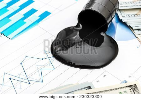 Crude Oil Spilled From Barrel And Money On The Financial Graphs. Business Concept.