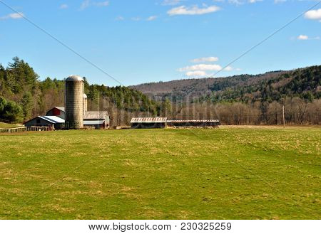 A Farm In A Freshly Mowed Field In Vermont With Mountains In The Background.