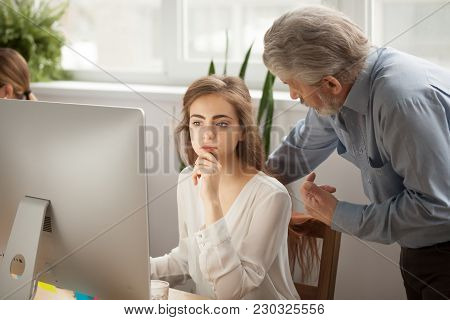 Senior Mentor Teaching Female Intern Using Computer In Office, Old Executive Training Young Focused